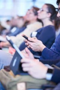 Lehrer und Lehrerinnen im Publikum halten Smartphones beim Digital Summit 2020. Einer Lehrerkonferenz zum Thema Digitalisierung