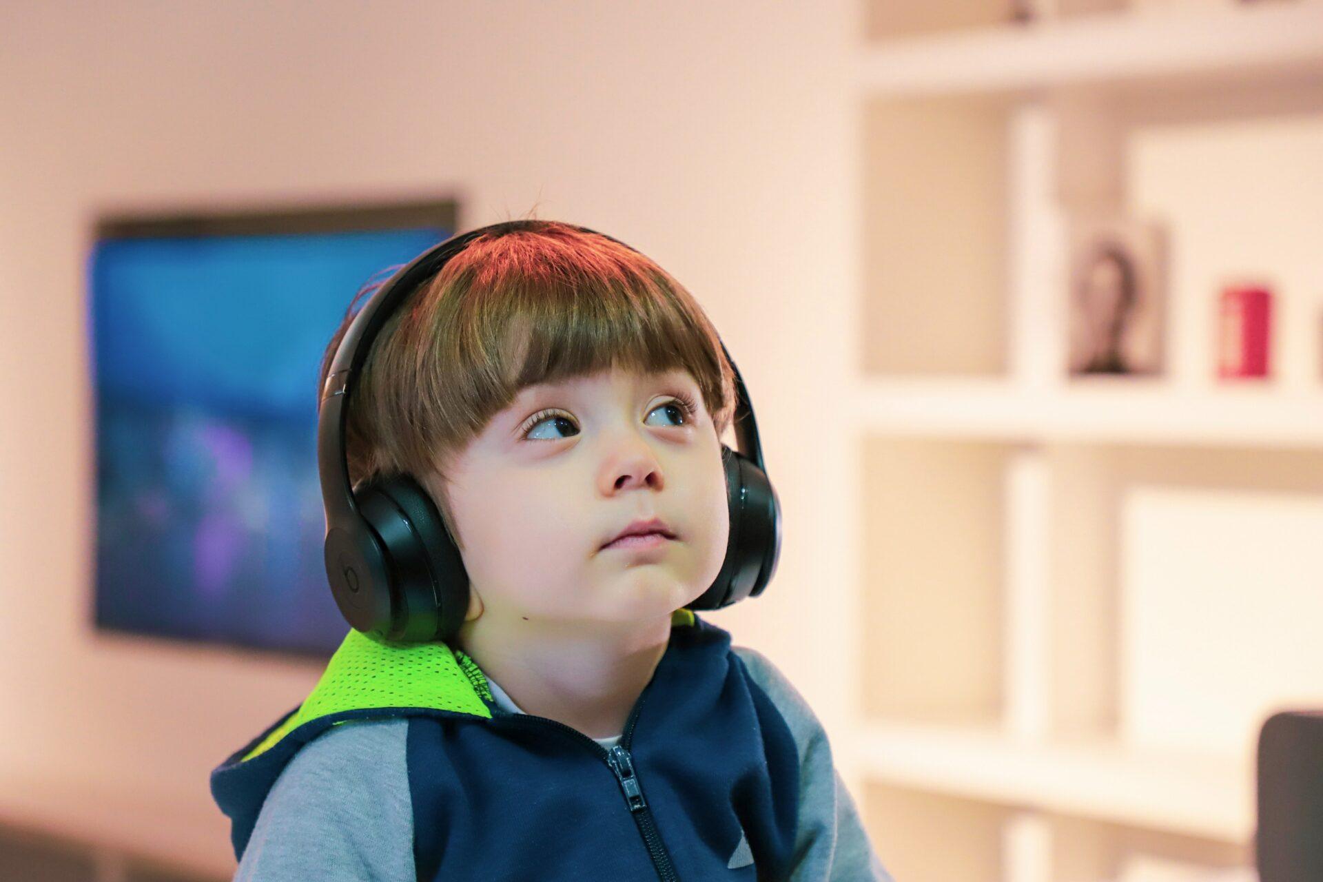 Junge mit trisomie 21 trägt Kopfhörer und hört Musik